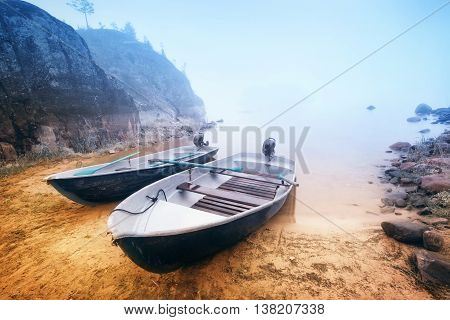 Boats in bay on the foggy lake