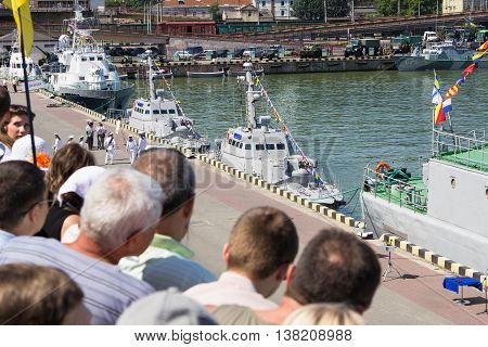 Odesa, Ukraine - July 03, 2016: people with flags on the docks of Odessa seaport during celebration Ukrainian NAVY day and the warships at the background