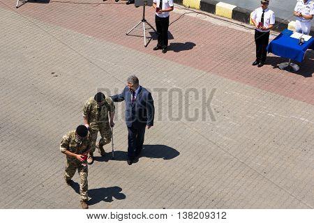 Odesa, Ukraine - July 03, 2016: President Petro Poroshenko helps wounded soldier after awarding. Navy day celebration in Odesa