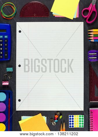 Lined Loose Leaf Paper With Frame Of School Supplies Over A Chalkboard Background