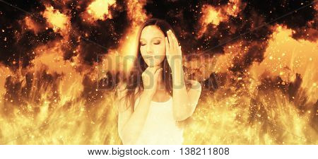 Young woman standing in front of a blazing inferno with a serene expression and eyes closed in meditation, wide angle panoramic banner
