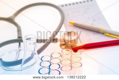 laboratory test tubes,medical glassware , Stethoscope  ,pen,notebook( Filtered image processed colorful effect. )