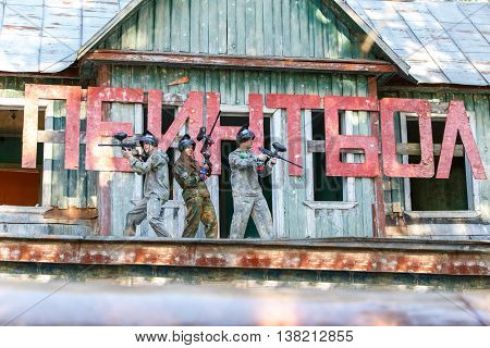 Three friends posing near giant sign with text paintball