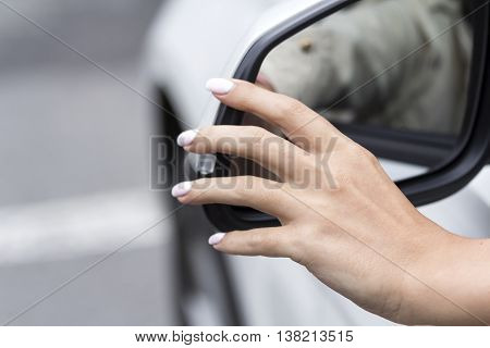 girl adjusts the rearview mirror in a white car