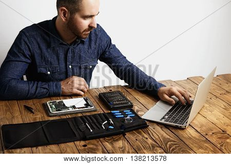 Professional uses laptop to find internet guides how to repair electronic device Tool bag with instruments and broken gadget near on vintage wooden table