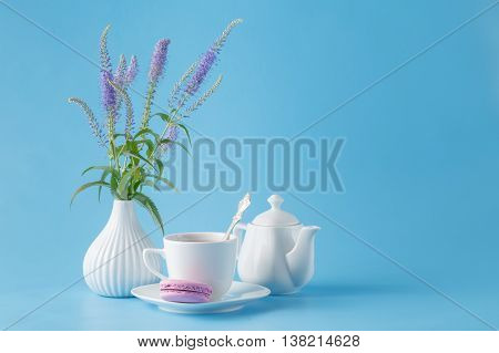 porcelain teacup and pink flowers on blue background
