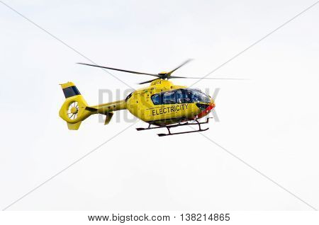 BATH UK - JULY 11 2016  Western Power Distribution Helicopter. Electricity service aircraft in flight inspecting power lines