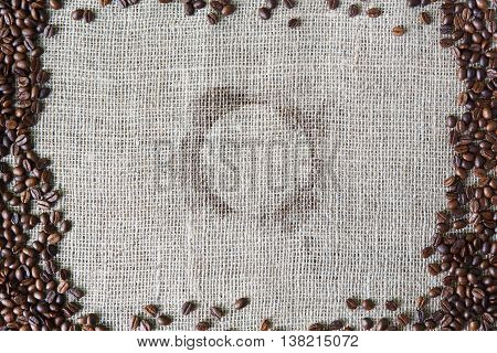 Burlap texture with coffee beans border. Sack cloth background with spot from coffee cup in the middle. Brown natural sackcloth canvas. Seeds at hessian textile