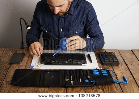 Professional is working in his lab to repair and clean computer laptop Toolkit box with specific instruments near