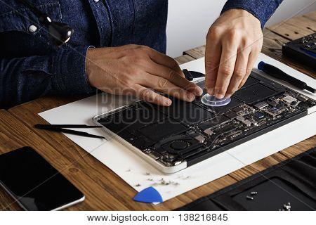 Master uses small suction cup to change battery cells from broken laptop to repair and clean it in his laboratory with specific toolkit on wooden table around close focus on hands.