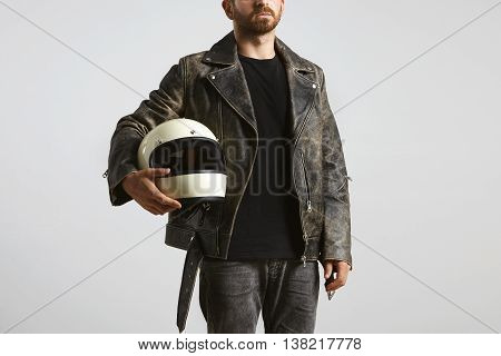 Brutal attractive bearded guy in weared oversized vintage motorcycle leather jacket and classic helmet in hand poses in black blank t-shirt from premium thin cotton, isolated on white mockup