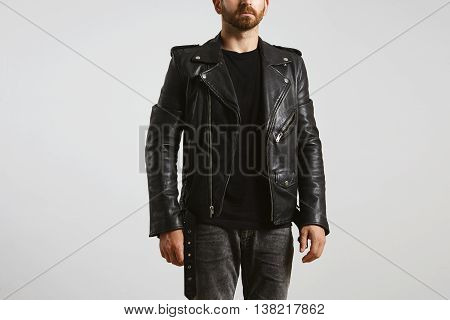Brutal attractive bearded biker in tailored motorcycle leather jacket poses in black blank t-shirt from premium thin cotton, isolated on white mockup