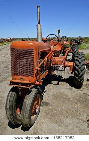 An old orange tractor is parked in salvage and a junkyard