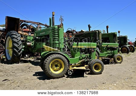 BARNSVILLE, MINNESOTA, June 15, 2016: The worn-out tractors and riding lawn mowers found in a junkyard are products of John Deere Co, an American corporation that manufactures agricultural, construction, forestry machinery, diesel engines, and drivetrains