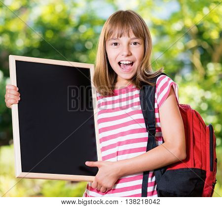 Outdoor portrait of happy girl 10-11 year old with big alarm clock and backpack. Back to school concept.