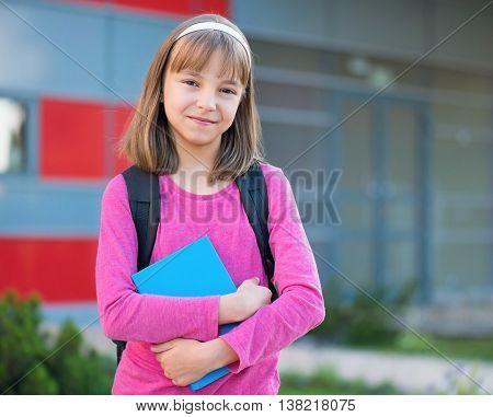 Happy girl holding books in school yard. Outdoor portrait.