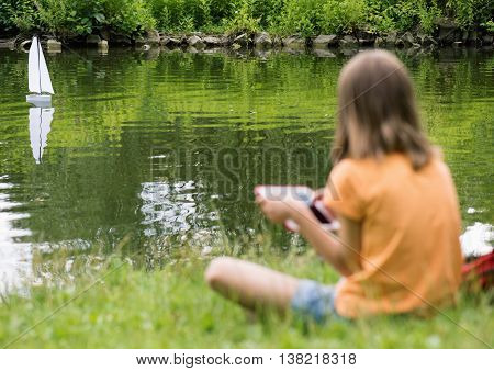 Girl playing with a remote controlled boat. Handmade model sailboat on lake - child with tablet. Out of focus girl. Selective focus limited to boat.