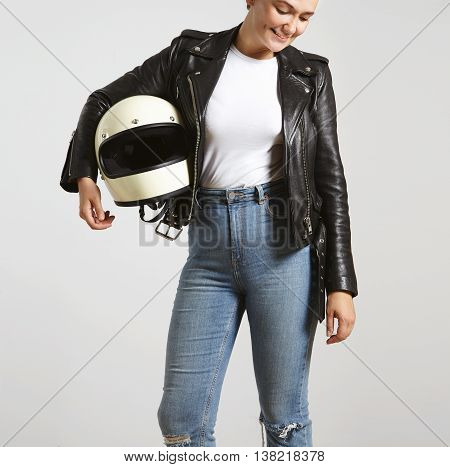 Young attractive woman in high waist jeans , leather motorbike jacket and blank white t-shirt with helmet in hand poses with smile looking down, isolated on white