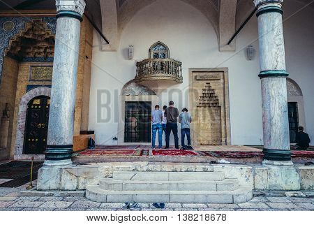 Sarajevo Bosnia and Herzegovina - August 23 2015. Men prays in front of 16th century Ottoman style Gazi Husrev-beg Mosque located at Bascarsija area in Sarajevo