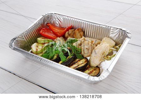 Healthy food and diet concept. Take away of fitness meal. Weight loss nutrition in foil boxes. Turkey meat slices with roasted grilled aubergine or eggplant and tomatoes at white wood