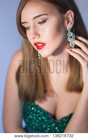 Elegant Posh Woman with Diamond Earrings. Platinum Jewelry with green Diamonds. Soft focus