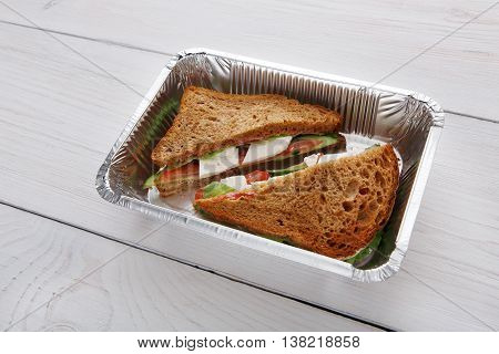 Healthy lunch and diet concept. Take away of fitness food. Weight loss nutrition in foil boxes. Sandwiches with whole-grain bread, cucumber, feta cheese and tomatoes at white wood