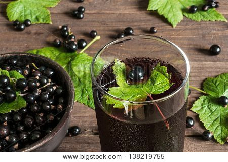 glass of cold black currant juice on wooden table with ripe berries in pottery bowl and green leaves around. high angle