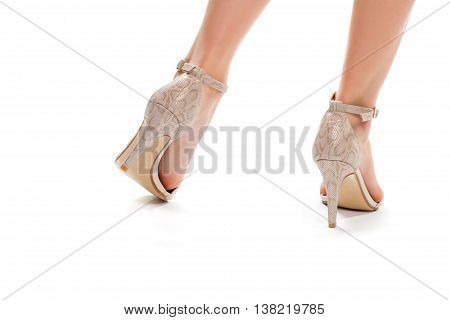 Woman's legs in heel shoes. Beige heels with straps. Girl's footwear on white background. Exclusive designer shoes.