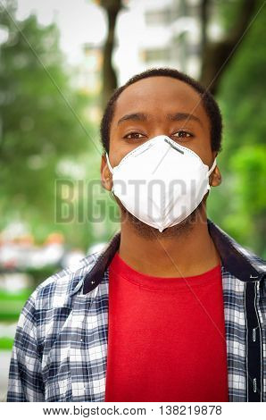 Closeup man wearing blue white square pattern shirt, covering nose and mouth with protection filter mask walking outside, blurry trees background.