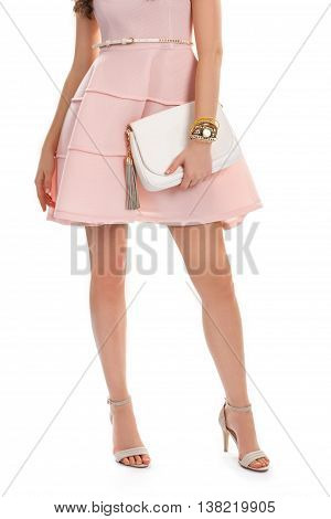 Girl wears salmon dress. Small wrist watch and purse. Beautiful clothing with accessories. Evening dress with small belt.