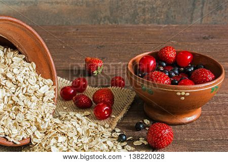 pile of oat flakes and berries in pottery on canvas on the table. close up. food background