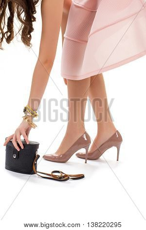 Female hand reaching for purse. Glossy shoes on heels. Black vintage bag with strap. Essential item for evening apparel.