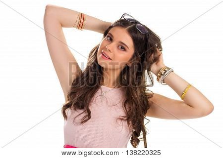 Woman touches hair. Girl with necklace and bracelets. Cute model in sleeveless dress. Slightly attractive gesture.