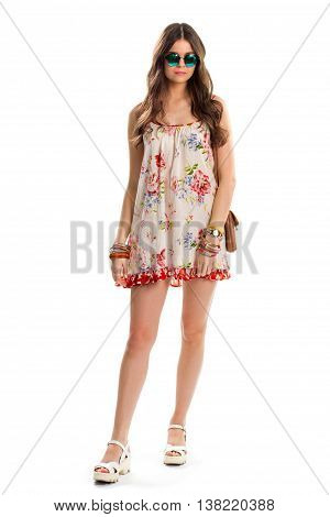 Woman in sleeveless floral dress. Dark green sunglasses and watch. Trendy look for summer. Red and blue flower print.