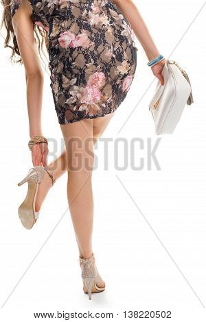 Woman touches her shoe. White handbag and floral dress. Fashionable dress with pink print. You must walk with confidence.