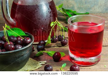 cold cherry juice in a glass and pitcher on wooden table with ripe berries in pottery bowl standing on canvas