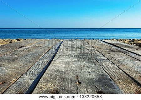 old wooden desk space with sand and sea on the beach. food photo montage background