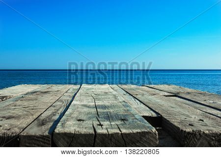 blurred sea background and old wooden desk table. photo montage background