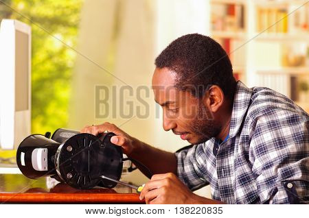 Man sitting by desk repairing small coffee maker using screwdiver, smiling happily while working.