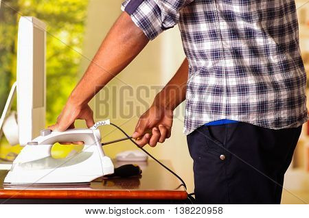 Man standing by desk repairing iron machine using screwdriver, window with garden background.