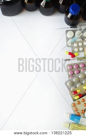 Background image of pills, capsules, tablets of different colors, hypodermics and thermometer over white