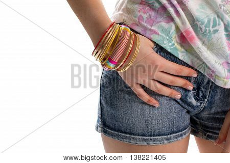 Lady's hand on shorts pocket. Blue denim shorts and bracelets. Casual accessories of bright color. Bracelet with striped pattern.