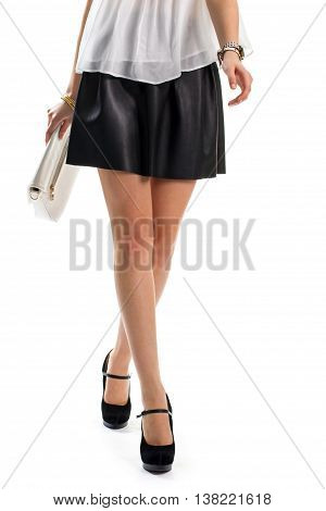 Lady in skirt is walking. Black skirt and white watch. Beautiful outfit with heel shoes. Leather handbag and suede footwear.