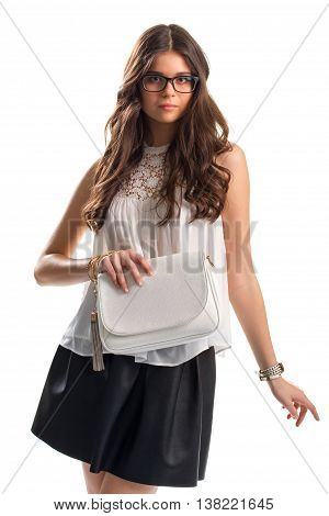 Young woman in blouse. Sleeveless white top and glasses. Plain purse and bracelets. Leather skirt of high quality.