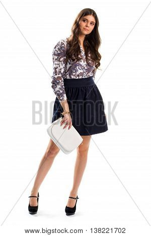 Woman wears floral shirt. Skirt and long sleeve shirt. Suede footwear of high quality. New collection of evening apparel.