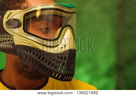 Closeup headshot man wearing green and black paintball protection facial mask covering entire face, transparent glass for windows.