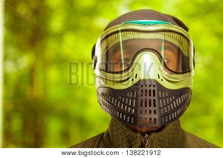 Closeup headshot man wearing jacket, green and black protection facial mask standing facing camera, forest background, paintball concept.