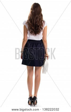 Girl wears white blouse. Back view of navy skirt. Clothing with shoes and accessories. White leather clutch bag.