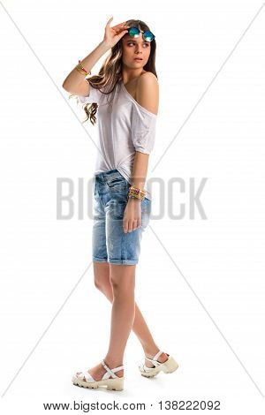 Young woman in white tunic. Wedge sandals and shorts. Summer outfit and accessories. What to wear on holidays.
