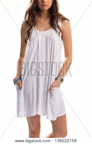Girl in white sarafan. Watch and set of bracelets. Simple garment with colorful accessories. Apparel for hot weather.